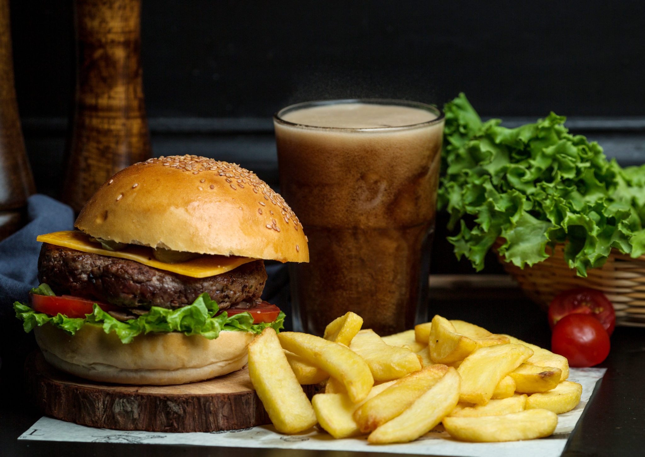 beef burger with cheese, lettuce, tomato served with fries and coke